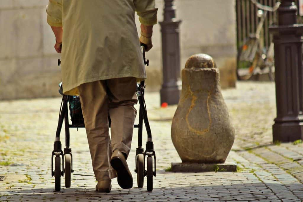 Old person walking with the help of a rollator walker
