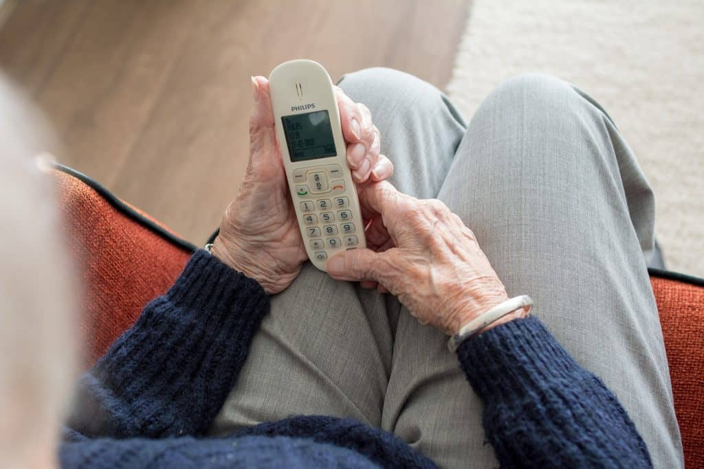 elderly women hold a home phone
